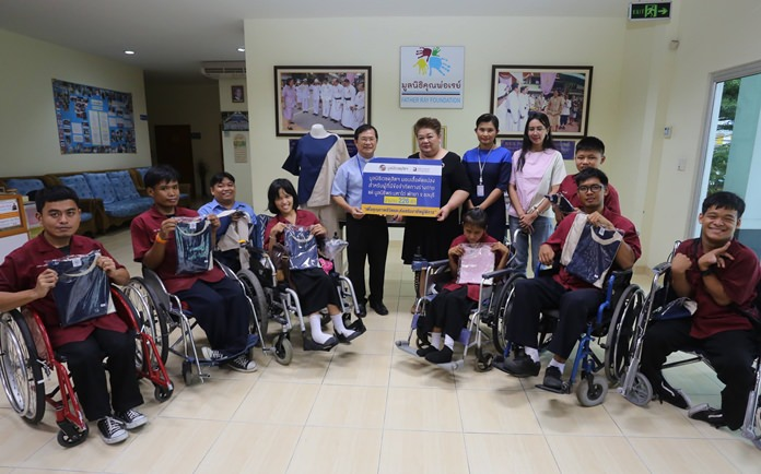 Hospital business development director Jutaporn Huyakorn presents specially tailored shirts, which students can put on and remove themselves, to Father Ray Foundation Vice President Rev. Michael Picharn Jaiseri at the Redemptorist School for Persons with Disabilities.