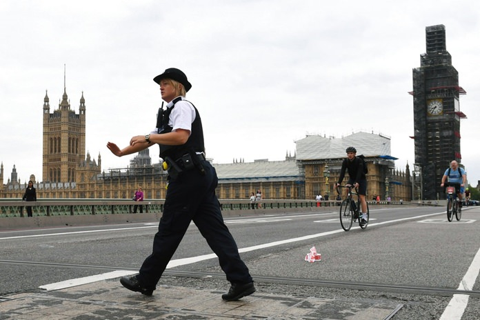 A police woman patrols on Westminster Bridge after a car crashed into security barriers outside the Houses of Parliament, in London, Tuesday, Aug. 14. (Stefan Rousseau/PA via AP)