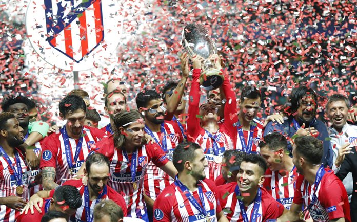 Atletico Madrid players hold the trophy and celebrate after the UEFA Super Cup final between Real Madrid and Atletico Madrid at the Lillekula Stadium in Tallinn, Estonia, Wednesday, Aug. 15. (AP Photo/Pavel Golovkin)