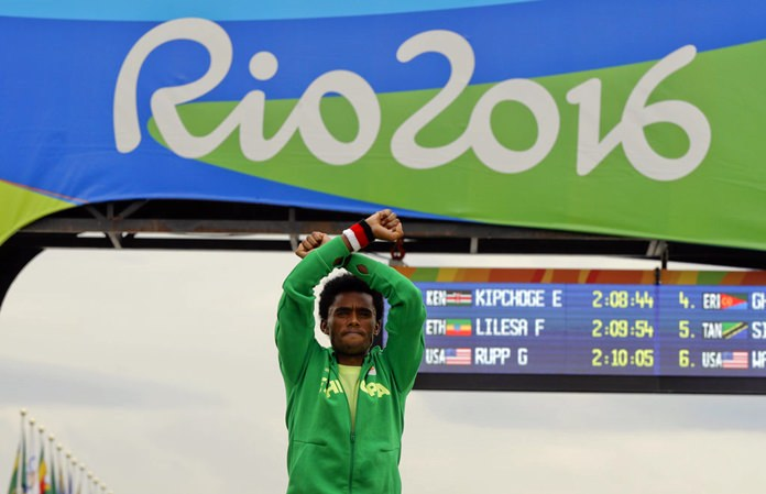 In this file photo dated Sunday, Aug. 21, 2016, silver medal winner, Ethiopia's Feyisa Lilesa, crosses his arms as he celebrates on the podium after the men's marathon at the 2016 Summer Olympics in Rio de Janeiro, Brazil. (AP Photo/Luca Bruno)