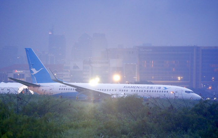 A Xiamen Air Boeing passenger plane from China lies on the grassy portion of the runway of the Ninoy Aquino International Airport after it skidded off the runway while landing Friday, Aug. 17, in suburban Pasay city southeast of Manila, Philippines. (AP Photo/Bullit Marquez)