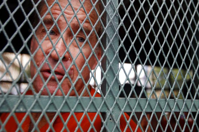 Australian filmmaker James Ricketson sits in a prison truck upon his arrival at Phnom Penh Municipal Court in Phnom Penh, Cambodia, Thursday, Aug. 16. (AP Photo/Heng Sinith)