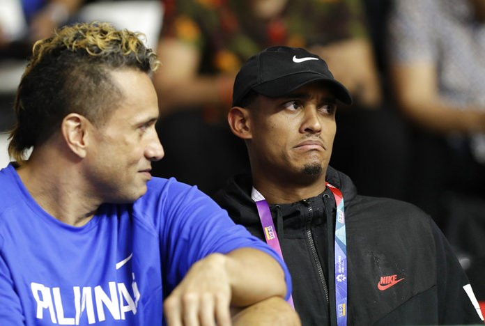 Filipino-American NBA player Jordan Clarkson, right, watches with Philippines' Pauliasi Taulava on the bench as the Philippines take on Kazakhstan in the men's basketball tournament at the 18th Asian Games in Jakarta, Indonesia on Thursday, Aug. 16. (AP Photo/Aaron Favila)