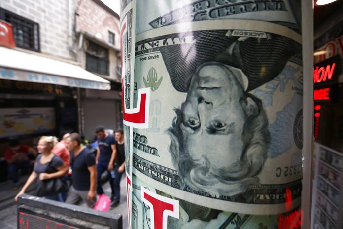 People walk past a currency exchange shop in Istanbul, Friday, Aug. 17. (AP Photo/Lefteris Pitarakis)