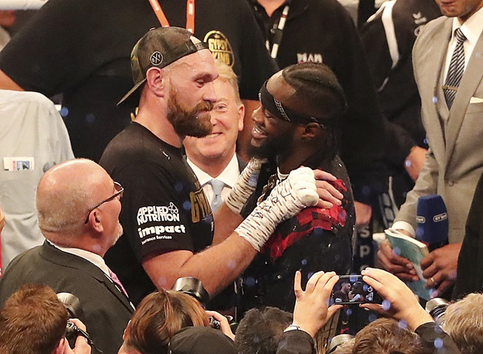 Tyson Fury, left, and WBC heavyweight champion Deontay Wilder face each other after Fury beat Francesco Pianeta during their heavyweight fight at Windsor Park in Belfast, Northern Ireland, Saturday Aug. 18. (Niall Carson/PA via AP)