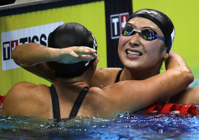 Japan's Rikako Ikee celebrates with teammate Tomomi Aoki, left, after winning the women's 100m freestyle final during swimming competition at the 18th Asian Games in Jakarta, Indonesia, Monday, Aug. 20. (AP Photo/Lee Jin-man)