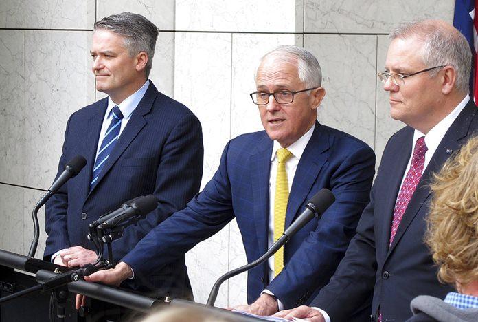 Australia's Finance Minister Mathias Cormann, left, Prime Minister Malcolm Turnbull, center, and Treasurer Scott Morrison address media at Parliament House in Canberra, Australia, Wednesday, Aug. 22. (AP Photo/Rod McGuirk)