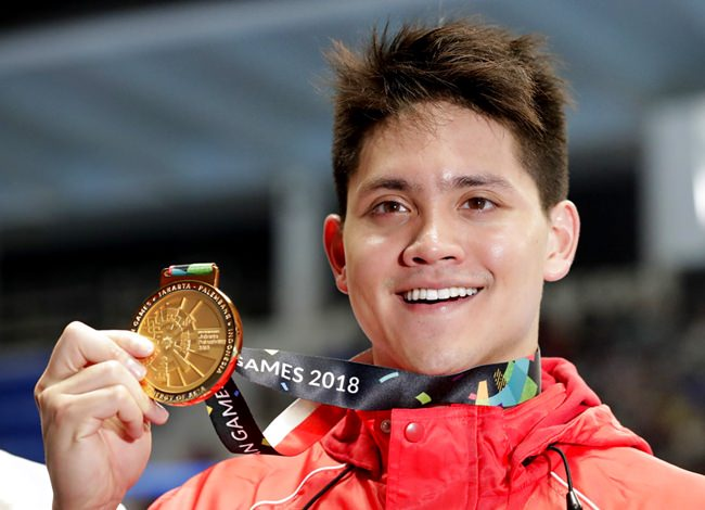 Singapore's Joseph Schooling holds up his gold medal for photographers after winning the men's 100m butterfly final at the 18th Asian Games in Jakarta, Indonesia, Wednesday, Aug. 22. (AP Photo/Lee Jin-man)