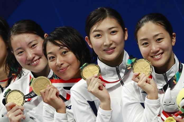 Japan's women's 4x100m medley relay team celebrate winning the gold medal during the swimming competition at the 18th Asian Games in Jakarta, Indonesia, Thursday, Aug. 23. (AP Photo/Bernat Armangue)