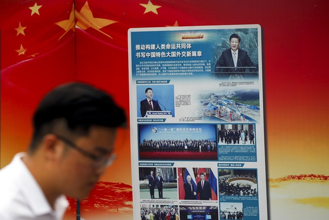 "A man walks by a government propaganda billboard promoting Chinese President Xi Jinping's signature ""One Belt One Road"" outside a subway station in Beijing, Tuesday, Aug. 28. (AP Photo/Andy Wong)"