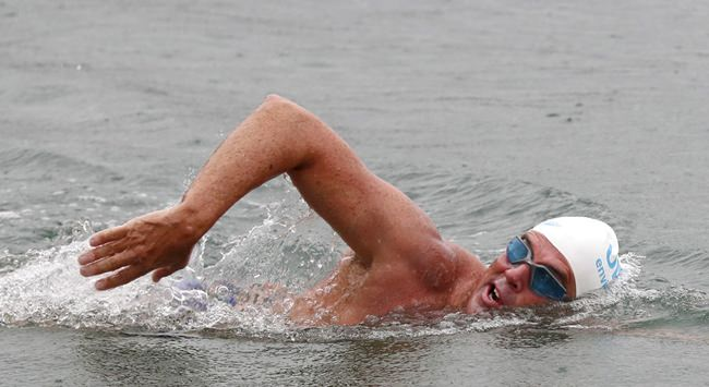 """Lewis Pugh he swims into Shakespeare Beach to complete his """"Long Swim"""" from Land's End to Dover, England, Wednesday Aug. 29, 2018. The Channel Swimming Association says endurance athlete Lewis Pugh completed on Wednesday his 330-mile (530-kilometer) swim along the length of the English Channel from Land's End to Dover _ the first swimmer to do so. (Gareth Fuller/PA via AP)"""