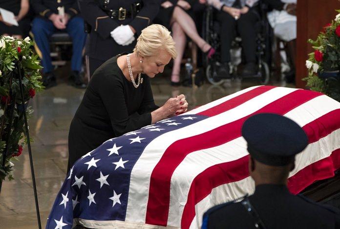 Cindy McCain, wife of Sen. John McCain, R-Ariz., leans over his flag-draped casket in the U.S. Capitol rotunda during a farewell ceremony, Friday, Aug. 31, 2018, in Washington. (AP Photo/J. Scott Applewhite)
