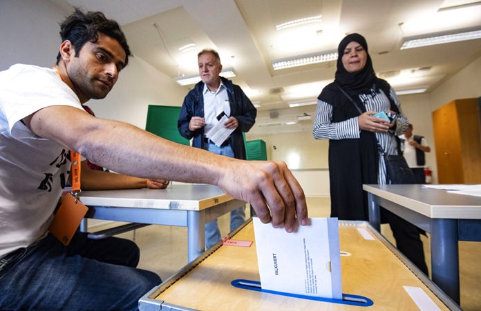 An Electoral counselor posts an election envelope in a polling station in Malmo, Sweden, Sunday Sept. 9, 2018. Polls have opened in Sweden's general election in what is expected to be one of the most unpredictable and thrilling political races in Scandinavian country for decades amid heated discussion around top issue immigration. (Johan Nilsson/TT via AP)