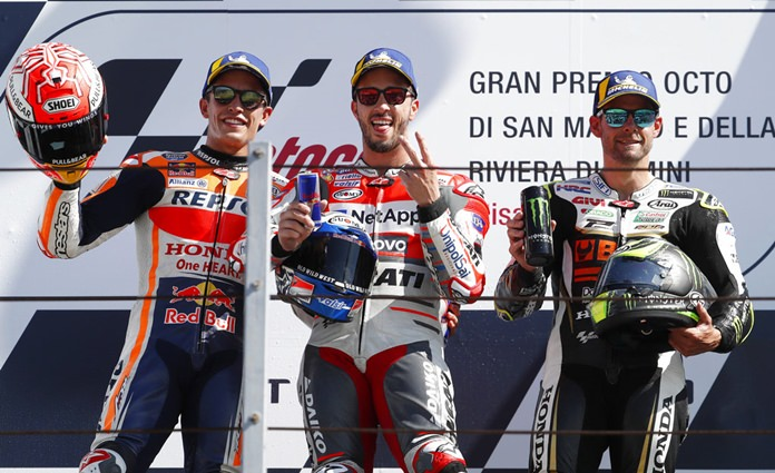 Italy's Andrea Dovizioso, the winner, is flanked on podium by runner-up, Spain's Marc Marquez and third placed Britain's Cal Crutchlow after the MotoGP race during the San Marino Motorcycle Grand Prix at the Misano circuit in Misano Adriatico, Italy, Sunday, Sept. 9, 2018. (AP Photo/Antonio Calanni)