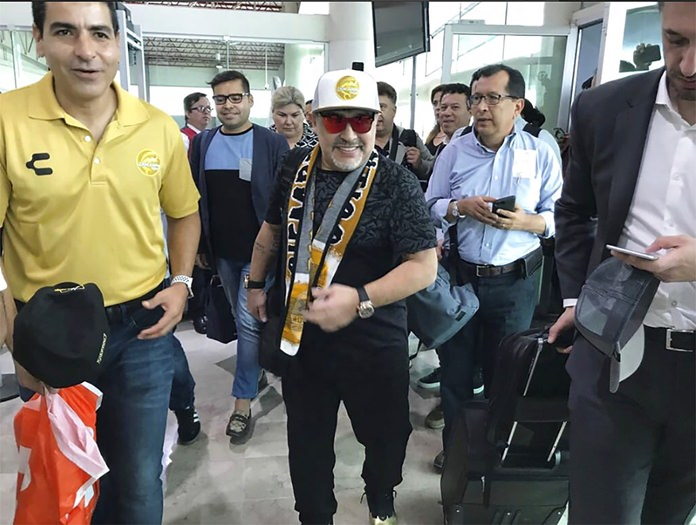 In this Sept. 8, 2018 file photo, Argentine soccer legend Diego Maradona walks through the airport in Culiacan, Mexico. Maradona, the soccer world's poster child for the perils of substance abuse, is setting up camp to lead a team in the heart of Mexico's drug cartel land. (Prensa Club Dorados de Sinaloa via AP, File)