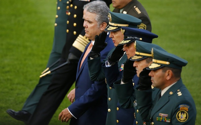 """In this Aug. 14, 2018 file photo, Colombia's President Ivan Duque reviews the troops, accompanied by his military staff during a ceremony in Bogota, Colombia. The rebel National Liberation Army said Monday, Sept. 10, that it was willing to """"liberate"""" a group of policemen and civilians it captured in August. But the rebels also accused President Ivan Duque of breaking promises made by his predecessor and said they will not accept his """"unilateral"""" conditions. (AP Photo/Fernando Vergara, File)"""