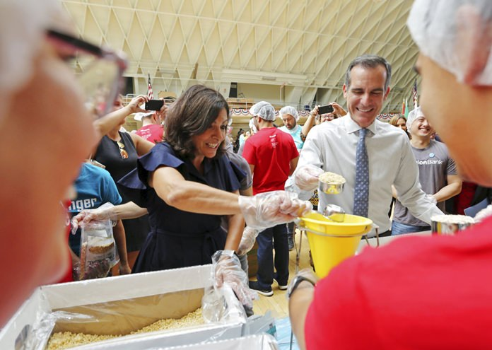 Paris Mayor Anne Hidalgo and Los Angeles Mayor Eric Garcetti help pack lunches for the needy following a ceremony marking the 17th anniversary of the Sept. 11, 2001 terrorist attacks on America, at the Los Angeles Fire Department's training center Tuesday, Sept. 11, 2018. (AP Photo/Reed Saxon)