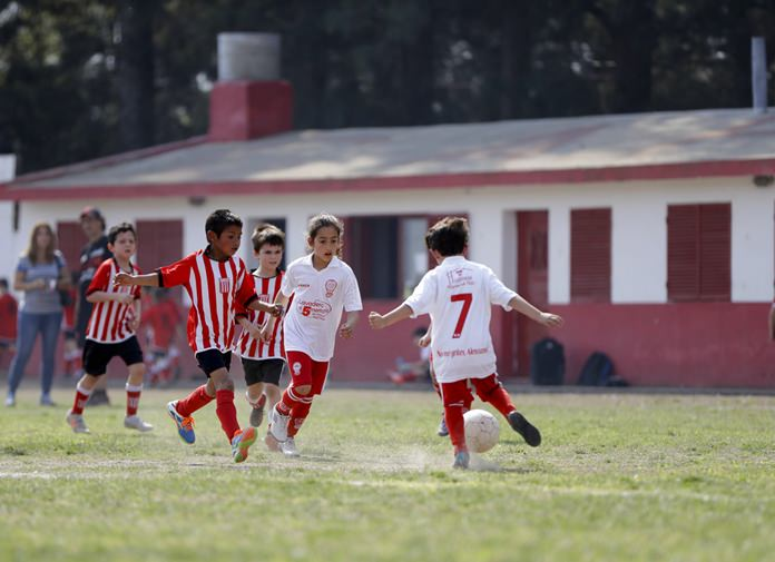 In this Sept. 8, 2018 photo Candelaria Cabrera, center, plays with her soccer teammates against the Alumni Club, in Chabas, Argentina. While she's officially now banned from playing with Huracan because she is a girl, the team has let her keep playing, at least until an opponent objects. (AP Photo/Natacha Pisarenko)