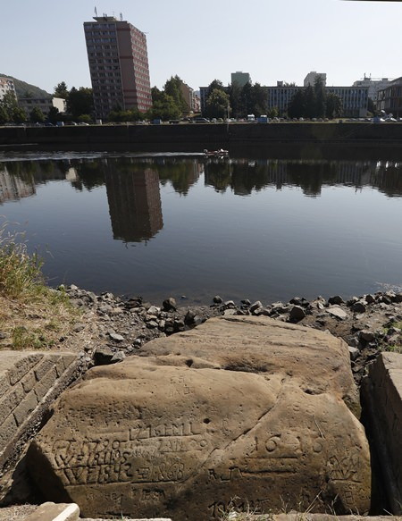 """On of the so called """"hunger stones"""" exposed by the low level of water in the Elbe River in Decin, Czech Republic, Thursday, Aug. 23, 2018. (AP Photo/Petr David Josek)"""