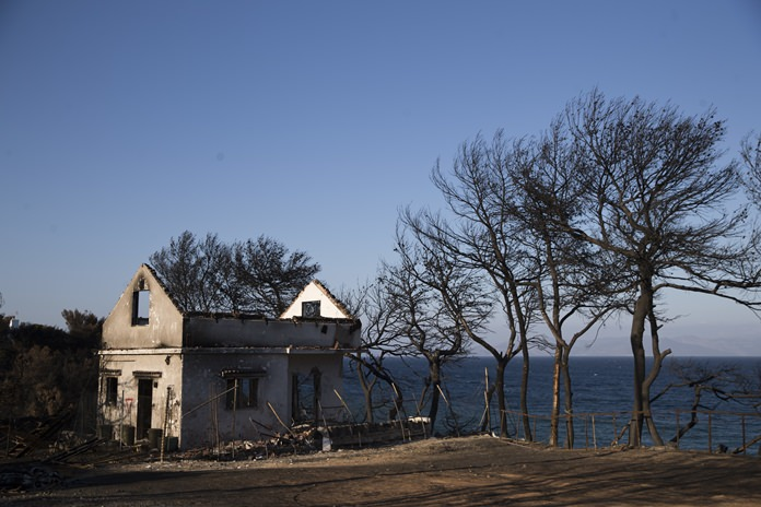 A destroyed house stand near the sea one month after a deadly wildfire tore through holiday homes near Athens, on at the seaside area of Mati. Authorities are still investigating the cause of the fire that killed more than 90 people and touched off a political spat that forced country's minister of public order to resign. (AP Photo/Petros Giannakouris)