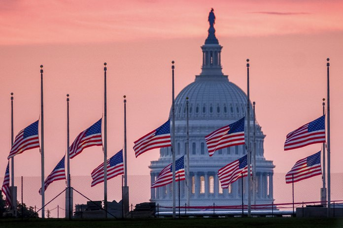 In this Aug. 26, 2018, file photo, flags flying a half-staff in honor of Sen. John McCain, R-Ariz., frame the U.S. Capital at daybreak in Washington. McCain, 81, died at his ranch in Arizona after a yearlong battle with brain cancer. (AP Photo/J. David Ake, File)