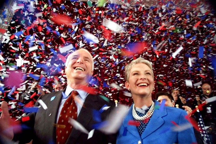 In this Jan. 30, 2000, file photo, confetti falls on Republican presidential hopeful Sen. John McCain, R-Ariz., and his wife, Cindy, at the end of their 114th New Hampshire town hall meeting with voters at the Peterborough Town House in Peterborough, N.H. (AP Photo/Stephan Savoia, File)