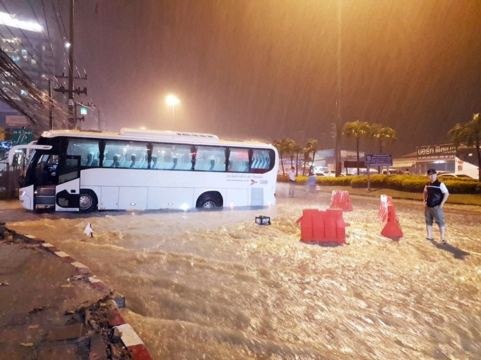 A Lotte Thailand Co. tour bus plunged into an open trench on Soi Photisan near Sukhumvit Road after raging storm runoff ironically washed away barriers erected by crews installing new flood-control pipes.