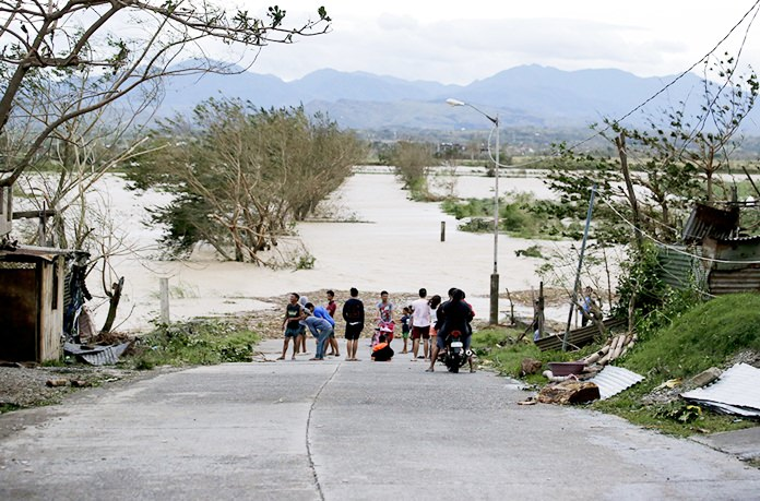 In this Saturday, Sept. 15, 2018, photo, residents stand by a flooded road following the onslaught of Typhoon Mangkhut in Tuguegarao City in Cagayan province, northeastern Philippines. (AP Photo/Aaron Favila, File)