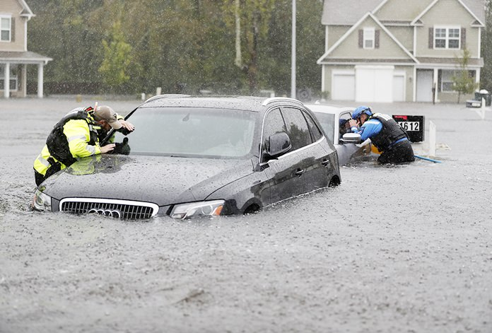 Members of the North Carolina Task Force urban search and rescue team check cars in a flooded neighborhood looking for residents who stayed behind as Florence continues to dump heavy rain in Fayetteville, N.C., Sunday, Sept. 16. (AP Photo/David Goldman)