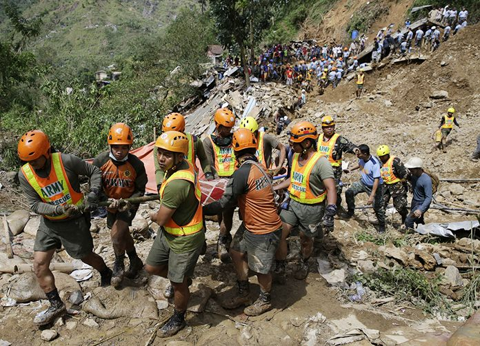 Rescuers carry a body recovered from a landslide caused by Typhoon Mangkhut in Itogon, Benguet province, northern Philippines on Monday, Sept. 17. Itogon Mayor Victorio Palangdan said that at the height of the typhoon's onslaught Saturday afternoon, dozens of people, mostly miners and their families, rushed into an old three-story building in the village of Ucab. The building, a former mining bunkhouse that had been transformed into a chapel, was obliterated when part of a mountain slope collapsed. (AP Photo/Aaron Favila)