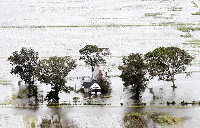 A farm house is surrounded by flooded fields from tropical storm Florence in Hyde County, N.C., Saturday, Sept. 15. (AP Photo/Steve Helber)