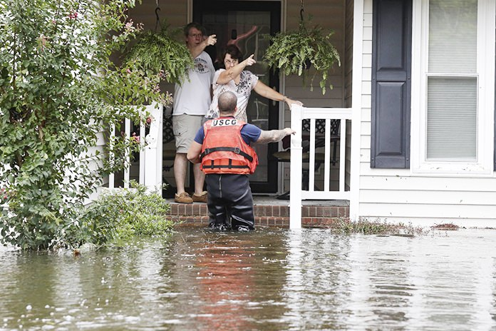 A member of the U.S. Coast Guard assists Roger and Susan Hedgepeth in Lumberton, N.C., Sunday, Sept. 16, following flooding from Hurricane Florence. (AP Photo/Gerry Broome)