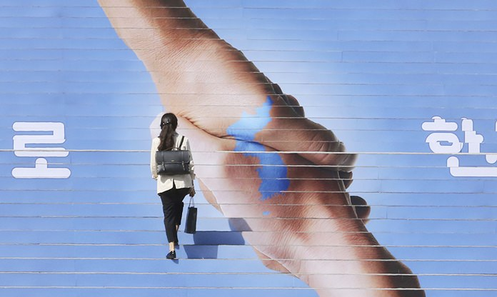 A woman passes by an image of two hands shaking to form the shape of the Korean Peninsula to mark the inter-Korean summit in Seoul, South Korea. (AP Photo/Ahn Young-joon, File)