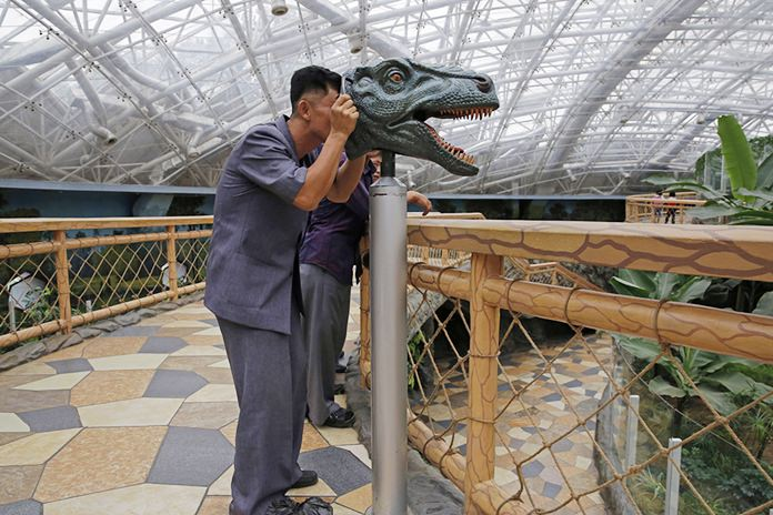 A North Korean man looks through a device to study the vision of a dinosaur, at the Central Zoo in Pyongyang, North Korea. (AP Photo/Kin Cheung, File)