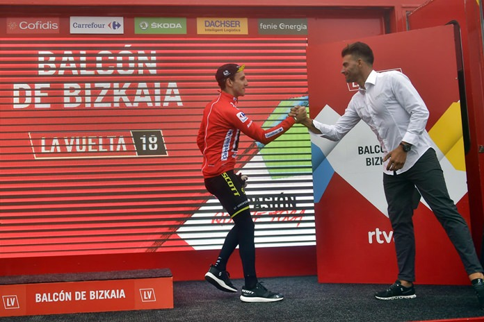 Mitchelton-Scott's Team Simon Yates of Great Britain, red shirt leader, is congratulated by La Vuelta staff member Oscar Pereiro at the end of the 17th stage between Getxo and Balcon de Vizcaya, 157 kilometers (97,55miles), of the Spanish Vuelta cycling race that finishes in Balcon de Vizcaya, northern Spain, Wednesday, Sept. 12, 2018. (AP Photo/Alvaro Barrientos)
