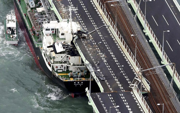 A tanker is seen after it slammed into the side of a bridge connecting the airport to the mainland, damaging part of the bridge and the vessel in Osaka, western Japan, Tuesday, Sept. 4, 2018. A powerful typhoon blew through western Japan on Tuesday, causing heavy rain to flood the region's main offshore international airport and high winds to blow a tanker into a connecting bridge, disrupting land and air travel. (Kentaro Ikushima/Mainichi Newspaper via AP)