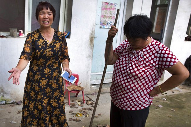 "In this July 11, 2018, photo, Xu Ying, left, stands with her neighbor at their home in Gucheng village in central China's Henan province. The AP spoke to the family Marip Lu, a young woman from Myanmar, accused of abusing her. The father, Li Qinggong, and mother, Xu Ying, (pictured) both denied Marip Lu had been abused or raped, and insisted she had not been purchased. But neither was able to explain how she'd ended up in their faraway village, or how she allegedly met and ""married"" their mentally disabled son, Li Mingming. (AP Photo/Ng Han Guan)"