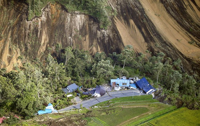 This aerial photo shows houses destroyed by a landslide after an earthquake in Atsuma town, Hokkaido, northern Japan, Thursday, Sept. 6, 2018. A powerful earthquake rocked Japan's northernmost main island of Hokkaido early Thursday, triggering landslides that crushed homes, knocking out power across the island, and forcing a nuclear power plant to switch to a backup generator. (Kyodo News via AP)