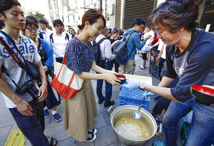 A worker of a restaurant near the area distributes soup following a powerful earthquake in Sapporo, Hokkaido, northern Japan Thursday, Sept. 6, 2018. Rescuers were rushing to unearth survivors and restore power Thursday after a powerful earthquake jolted Japan's northernmost main island of Hokkaido, buckling roads, knocking homes off their foundations and causing entire hillsides to collapse. (Hiroki Yamauchi/Kyodo News via AP)