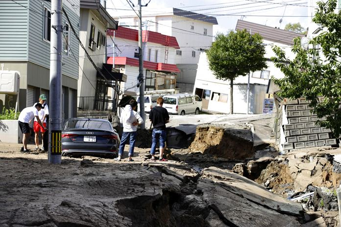 Residents watch a road damaged by an earthquake in Sapporo, Hokkaido, northern Japan, Thursday, Sept. 6, 2018. A powerful earthquake shook Japan's northernmost main island of Hokkaido early Thursday, causing landslides that crushed homes, knocking out power across the island. (Hiroki Yamauchi/Kyodo News via AP)
