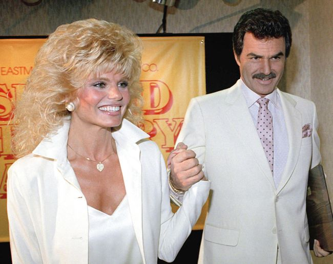FILE - In this March 27, 1987 file photo, Burt Reynolds, right, holds hands with Loni Anderson at luncheon in Los Angeles (AP Photo/Bob Galbraith, File)