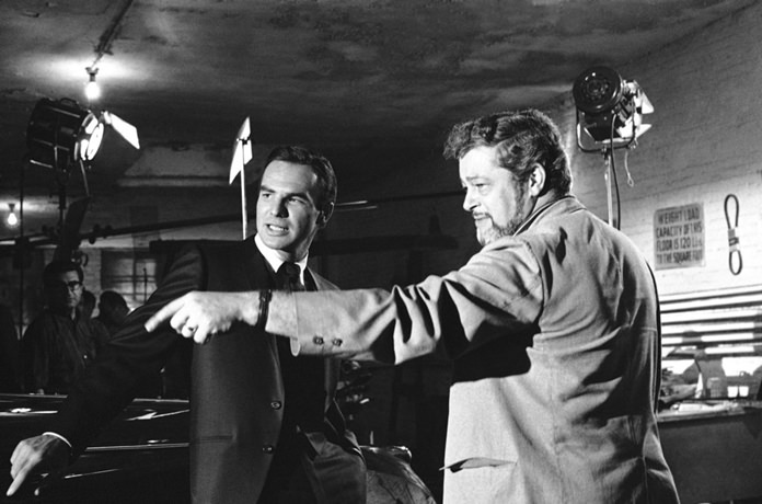 """In this May 27, 1966 file photo, actor Burt Reynolds, left, discusses a scene with director Paul Bogart during location shooting of a new ABC-TV series """"Hawk"""", in New York. (AP Photo/Joe Caneva, File)"""
