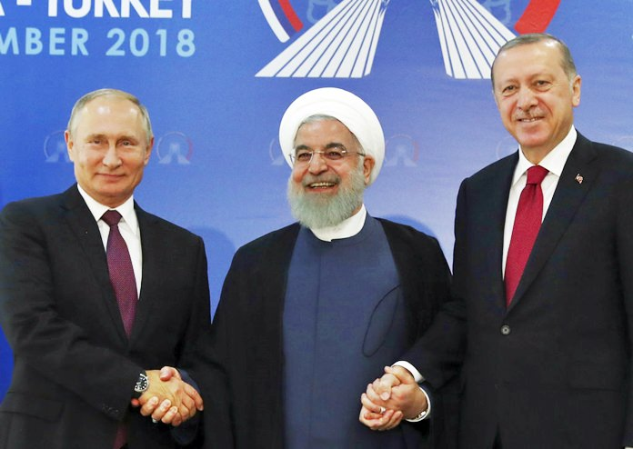 Iran's President Hassan Rouhani, centre, flanked by Russia's President Vladimir Putin, left, and Turkey's President Recep Tayyip Erdogan, pose for photographs in Tehran, Iran, ahead of their summit to discuss Syria, Friday, Sept. 7, 2018. The three leaders began a meeting to discuss the war in Syria.(Presidential Press Service via AP, Pool)