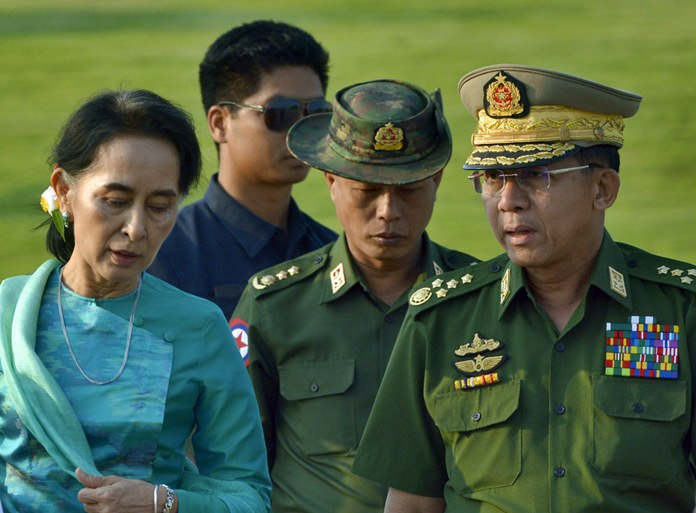 In this May 6, 2016, file photo, Aung San Suu Kyi, Myanmar's foreign minister and de facto leader, left walks with senior General Min Aung Hlaing, Myanmar's commander-in-chief, right, in Naypyitaw, Myanmar. Myanmar's government looks as if it's under siege from an international community concerned about the condition of its nascent democracy, with widespread calls for a genocide tribunal to hold its military to account for the brutal treatment of its Muslim Rohingya minority. (AP Photo/Aung Shine Oo, File)