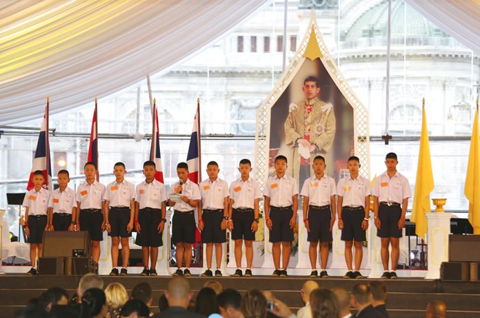 """Members of the Wild Boars soccer team give their thanks during and event in front of the image of His Majesty King Maha Vajiralongkorn Bodindradebayavarangkun during the event titled """"United as One"""" Bangkok, Thailand, Thursday, Sept. 6, 2018. Lalit)"""