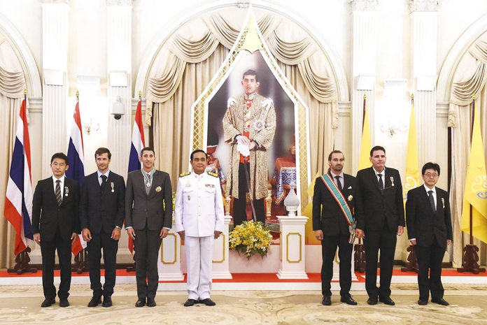 From left, Japanese cave diver Shigeki Miyake, Belgian cave diver Ben Reymenants, American cave diver Joshua David Morris, Thai Prime Minister Prayuth Chan-ocha, Finnish cave diver Mikko Paasi, American cave diver Bruce Konefe and Japanese cave diver Shigeki Miyake pose in front of an image of His Majesty King Maha Vajiralongkorn at the Royal Decoration Ceremony for aiding the rescue of the Wild Boars soccer team trapped for almost three weeks in a flooded cave, at the Royal Thai Government House in Bangkok Friday, Sept. 7, 2018. (Lillian Suwanrumpha/Pool Photo via AP)