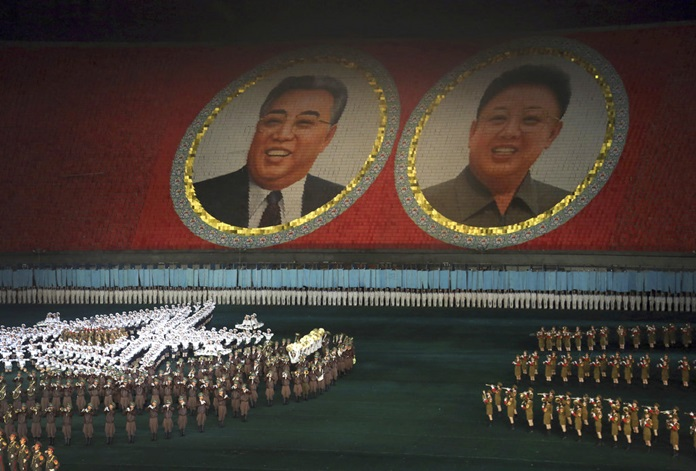 """In this July 22, 2013, file photo, performers dance in front of portraits of late North Korean leaders Kim Il Sung, left, and Kim Jong Il in Pyongyang, North Korea. North Korea is bringing back one of its most iconic art forms - mass games performed by tens of thousands of people working in precise unison - to mark its 70th anniversary on Sunday, Sept. 9, 2018. The performance, which takes months if not years of intense preparation and training, is being called """"Glorious Country"""" this year. (AP Photo/Wong Maye-E, File)"""