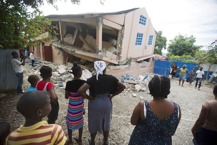 Residents stand looking at a collapsed school damaged by a magnitude 5.9 earthquake the night before, in Gros Morne, Haiti, Sunday, Oct. 7. (AP Photo/Dieu Nalio Chery)