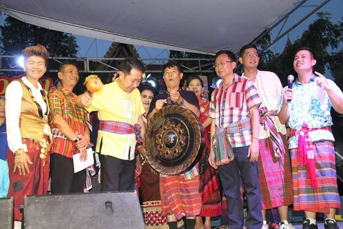 Banglamung District Chief Naris Niramaiwong strikes the gong to begin the festivities as Amnat Theingtham, President of Pattaya Issan Association and other honored guests look on.