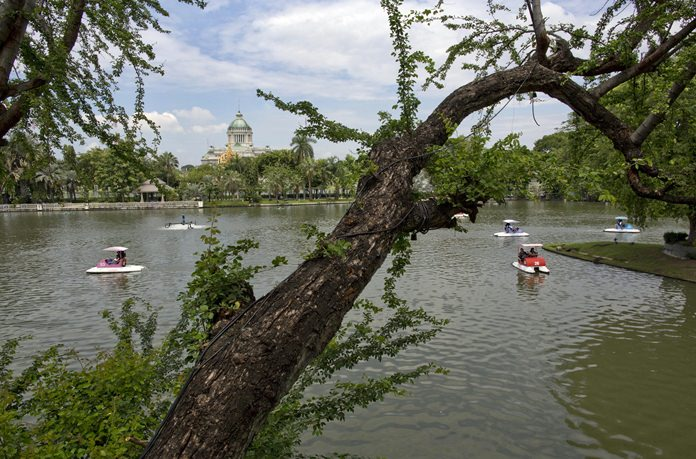 Visitors paddle boats in a lake at Dusit Zoo, as the Ananta Samakhom Throne Hall in looms over them in the background. (AP Photo/Gemunu Amarasinghe)